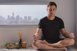 Mindful healthy mature asian man practicing meditation at home sitting on the floor doing yoga for mental balance relaxing on stress and enjoying time away from technology.